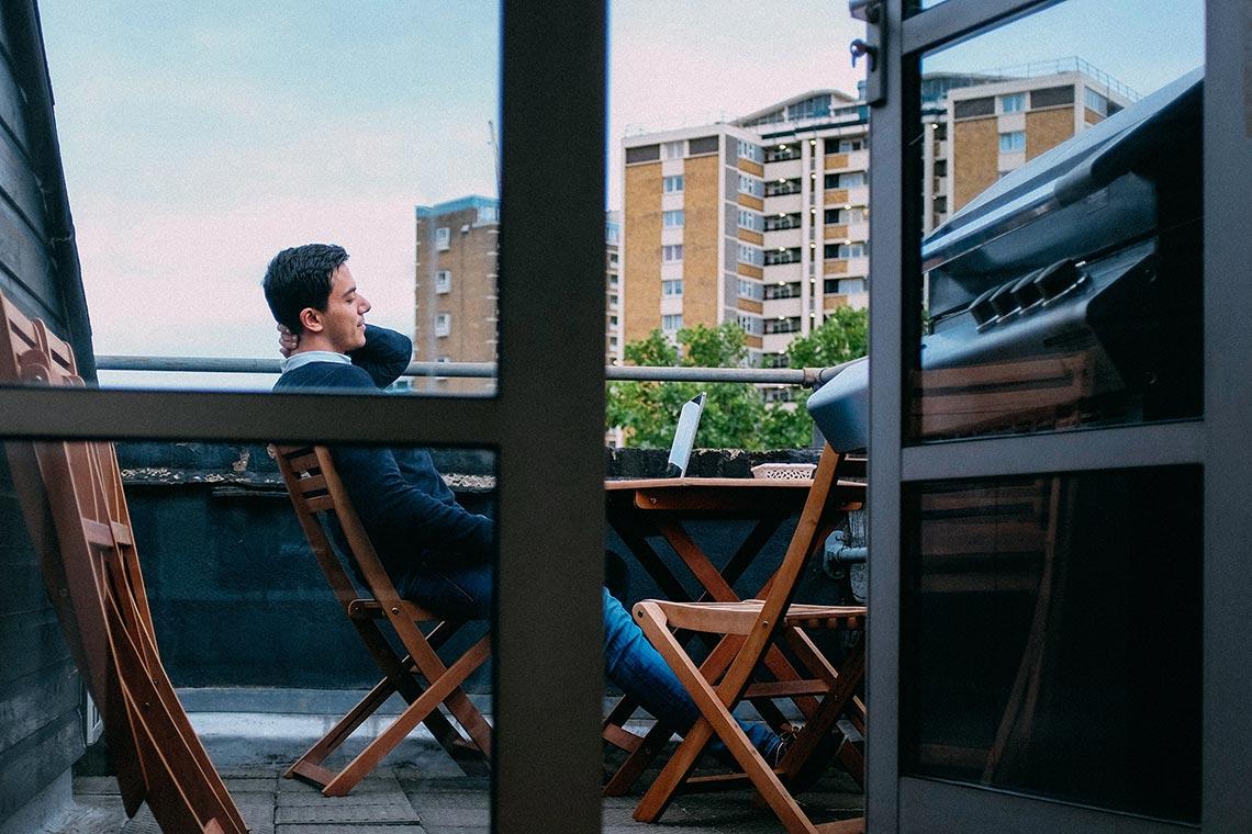 Ein Mann sitzt auf einem Balkon und entspannt